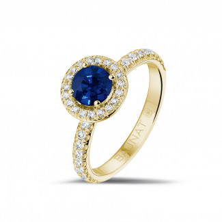 Halo solitaire ring in yellow gold with a round sapphire and small diamonds