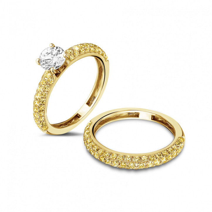 Matching engagement and wedding band in yellow gold with a central diamond of 0.70 carat and small yellow diamonds