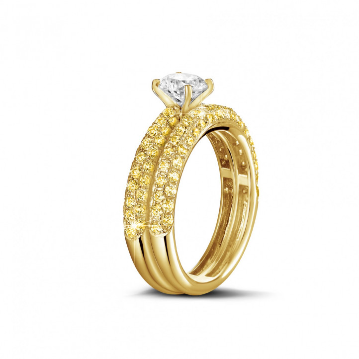 Matching engagement and wedding band in yellow gold with a central diamond of 1.00 carat and small yellow diamonds