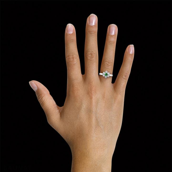 Anillo flor en Platino con esmeralda redonda y diamantes en los lados