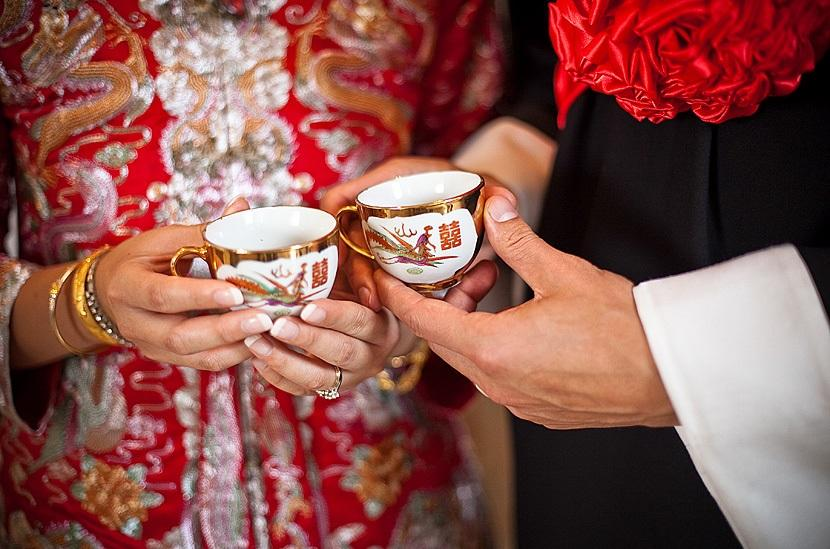 Chinese couple in red holding red tea cups for their wedding ceremony - BAUNAT