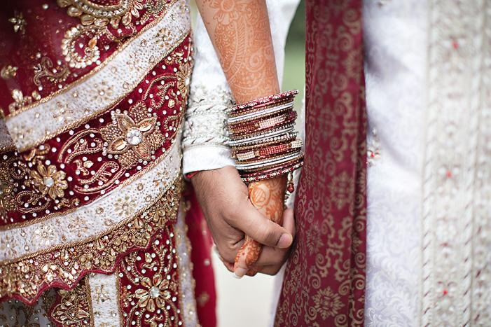 Indian newlyweds holding hands with bracelets instead of golden rings - BAUNAT
