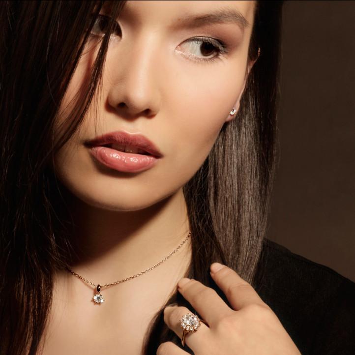 0.90 karaat entourage ring in rood goud met ovale diamant